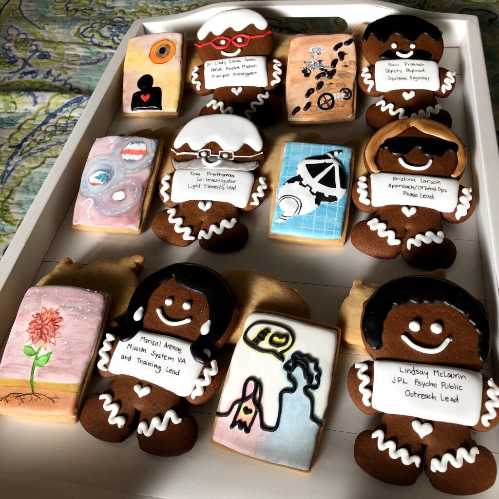 Six gingerbread men and six rectangular butter cookies lay in a checkered pattern. Each gingerbread man is decorated with the name of a Psyche Mission member, and their respective butter cookie is decorated with watercolor symbols to represent a lesson learned from them. The pairs are ordered by row: 1 - Marisol Arenas, Lindsay McLaurin; 2 - Tom Prettyman, Kristina Larson; 3 - Dr. Lindy Elkins-Tanton, Ravi Prakash.