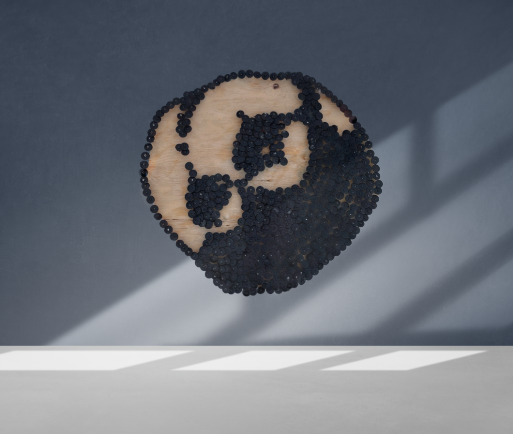 A sculpture of the Psyche asteroid hangs on a wall blue wall. The sculpture is made out of wood and black circular nail caps, which form two large craters. The nail caps also form Psyche's ridges and shadows.