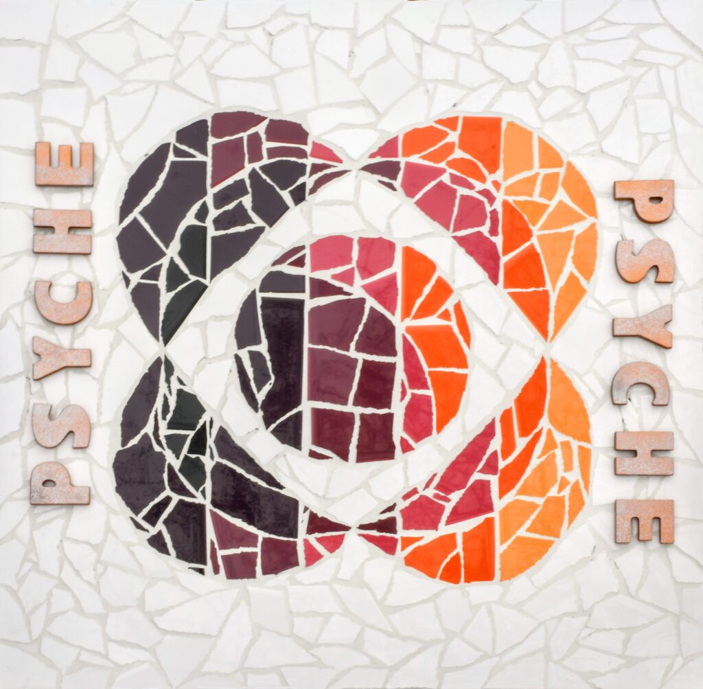 "White, orange, pink, and purple ceramic tiles arranged in the shape of the Psyche logo with white grout finish and silver spray-painted wooden ""Psyche"" letters."