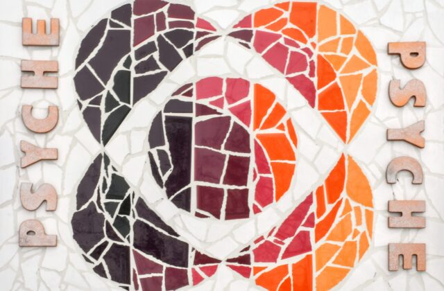 """White, orange, pink, and purple ceramic tiles arranged in the shape of the Psyche logo with white grout finish and silver spray-painted wooden """"Psyche"""" letters."""