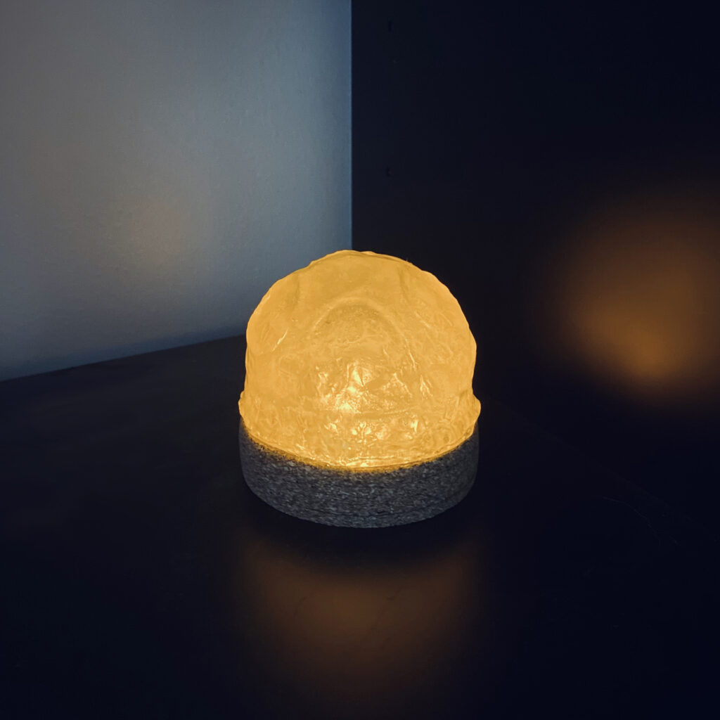 """A product presentation page, titled """"Psyche Light"""". In the center of the page is a large photograph of a lamp. The lamp has a short, cylindrical base made of cork. A translucent white dome sits on the base and diffuses an orange light. The dome is heavily textured with craters to mimic the hypothesized surface of the asteroid Psyche. Along the left margin is a black and white orthographic line drawing of the lamp."""