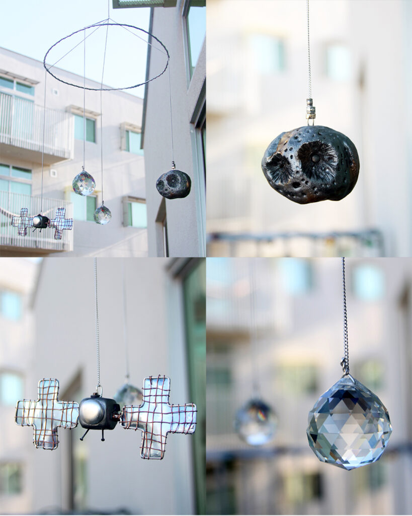 This is a hanging mobile made from wire, with clay pieces of Psyche and the satellite hanging by chains. They are painted in a shiny metallic paint that shimmers in the sun and are hanging with two sun catcher crystals.