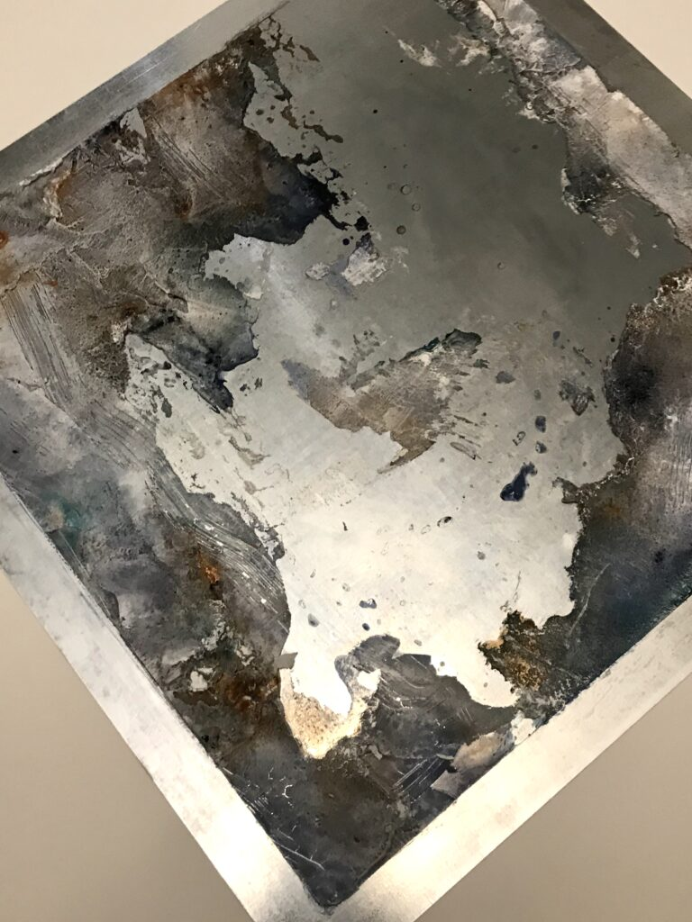 A metallic aluminum sheet with scattered abstract paste throughout the piece. The colors are grey, purple, and copper.
