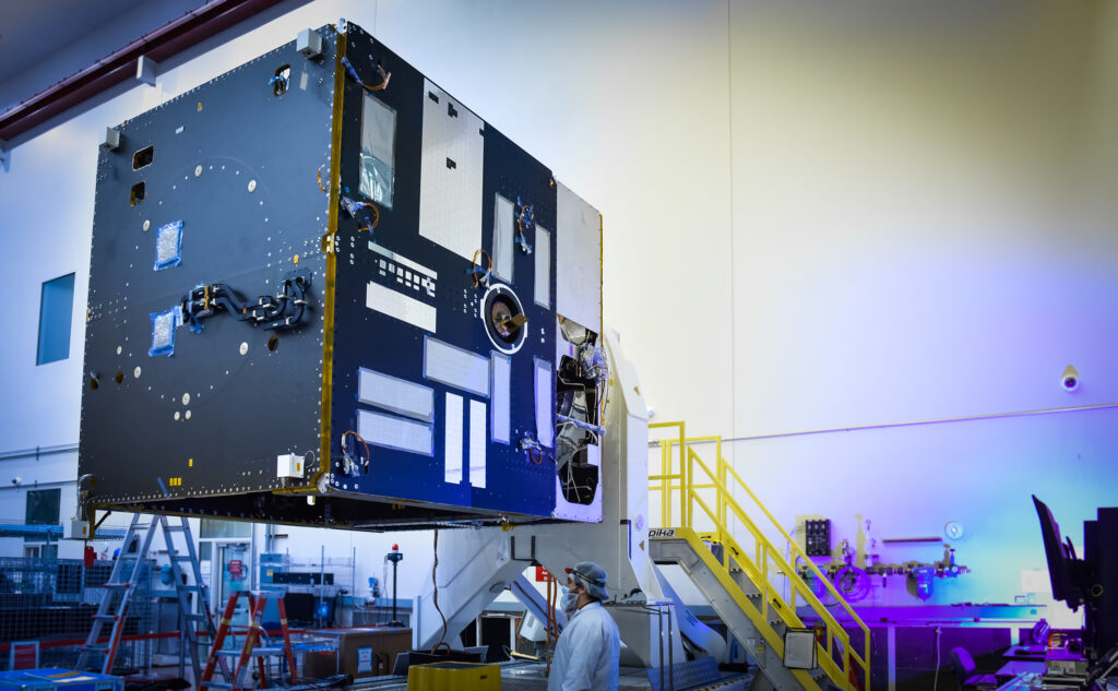 This image is of the black and silver main body of the Psyche Spacecraft. The equipment panels have been mated to Psyche's propulsion module and technicians will soon begin installing attitude control components.