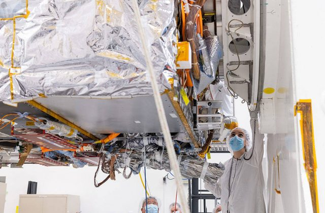 This image is a closeup underside view of the main body of the spacecraft (the bus) with a engineers nearby inspecting hardware.