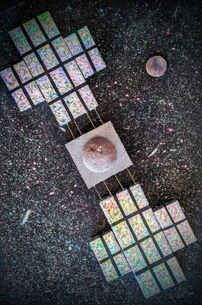 This piece is a multimedia painting of the Psyche spacecraft as it approaches the Psyche asteroid. The background is made up of many different colors of acrylic paint splattered on to a wooden canvas. The spacecraft is made up of styrofoam and metal wire, and it is decorated with different metallic paints.