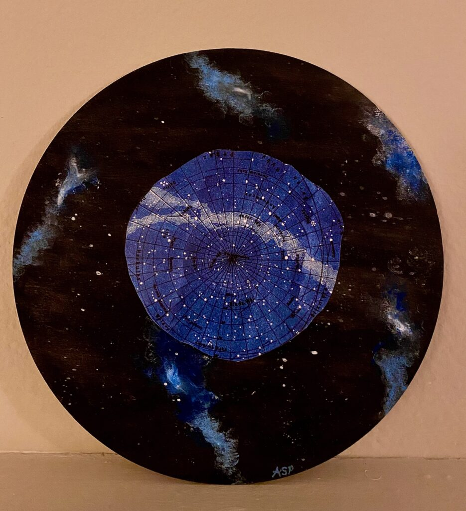 Psyche and the Night Sky is created on a circular wooden panel with acrylic paint. The background is the night sky with blue nebulas floating around Psyche, which is cut out of a constellation map.