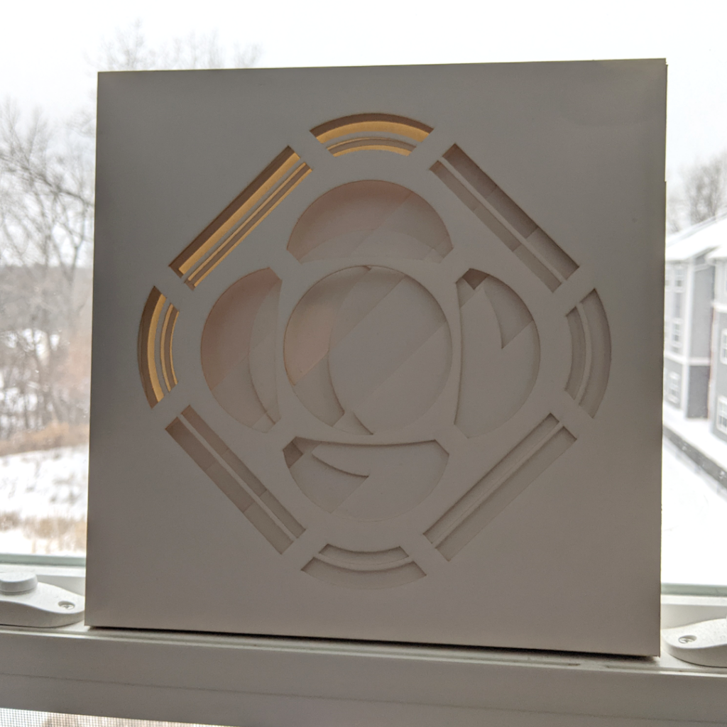 A paper lightbox of the Psyche logo that is divided into multiple layers, which indivudually appear to be abstract shapes. When viewed from the front, the layers line up to depict the Psyche logo. The lighting causes the box to go from a lighter shade in the top left to a darker shade in the bottom right.
