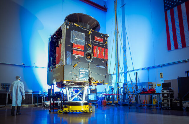 This image is of the main body of the spacecraft (the bus) in a factory space with a technician standing nearby.