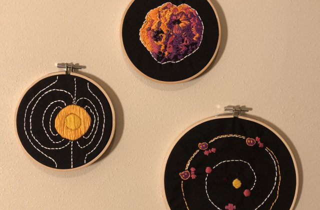 Three embroidery hoops of black fabric lay arranged as a triangle on an off-white wall. The top hoop has an embroidered asteroid colored with yellow, orange, pink, and purple threads. The bottom left hoop has a yellow threaded circle with unsymmetrical white dashed lines following the arc of the circle from the top most point to the bottom most point. The bottom right hoop is slightly bigger with an orbital design of the Sun, Mercury, Venus, Earth, Mars and the Psyche asteroid and spacecraft at three spots. A white dashed line circles from Earth to Mars then around to a greater orange outer circle where Psyche and the spacecraft meet.