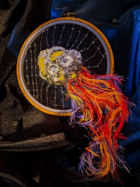 The Psyche asteroid embroidered with silver stitching to represent magnetic fields. A trail follows behind Psyche and off of the embroidery wheel.