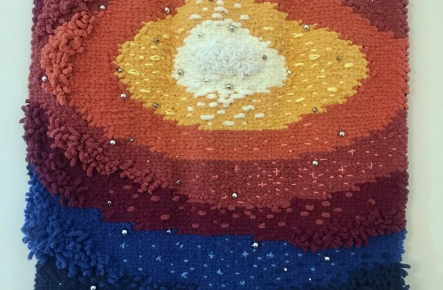 A full view of a tapestry of woven yarn in dark blue, light blue, red, light red, orange, yellow, and cream.