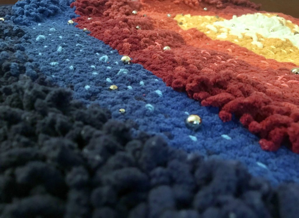 A close-up view of a tapestry of woven yarn in dark blue, light blue, red, light red, orange, yellow, and cream.
