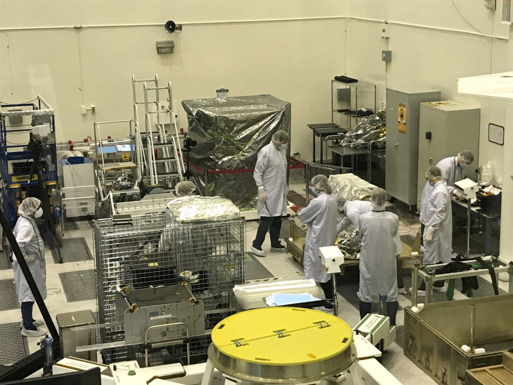 Engineers in a large room surrounded by technical equipment