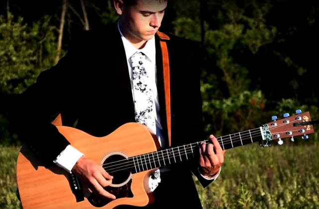 Photo of Mitchel Medvec playing a guitar in a wooded field