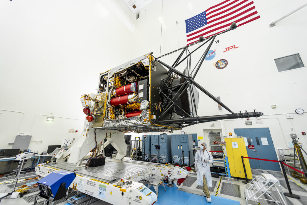 panoramic view of JPL's High Bay 2 area showing the bus (body) of the spacecraft and some engineers