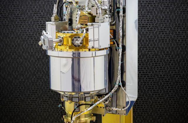 Image showing the gamma-ray spectrometer component of the GRNS instrument. It has a large central cannister with many wires and cables on a metal stand.