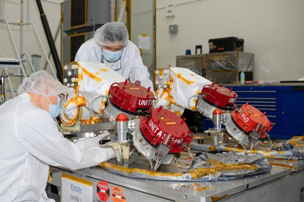 Engineers at NASA's Jet Propulsion Laboratory in Southern California prepare to integrate four Hall thrusters (beneath red protective covers) into the agency's Psyche spacecraft in July 2021.