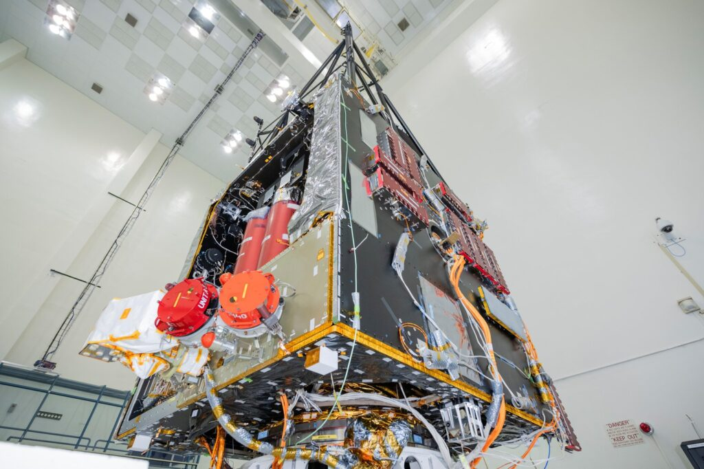 Two thrusters are visible beneath red round protective covers, after being integrated into the spacecraft.